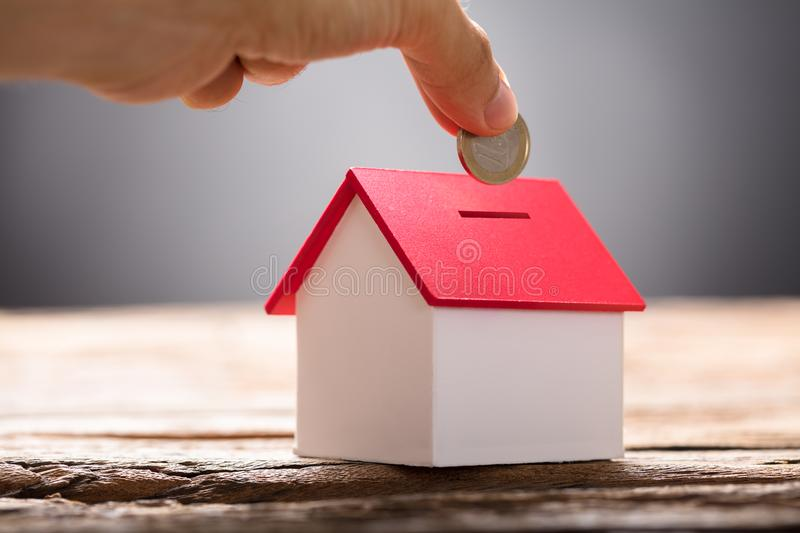 Hand Putting Coin In House Piggy Bank royalty free stock photo