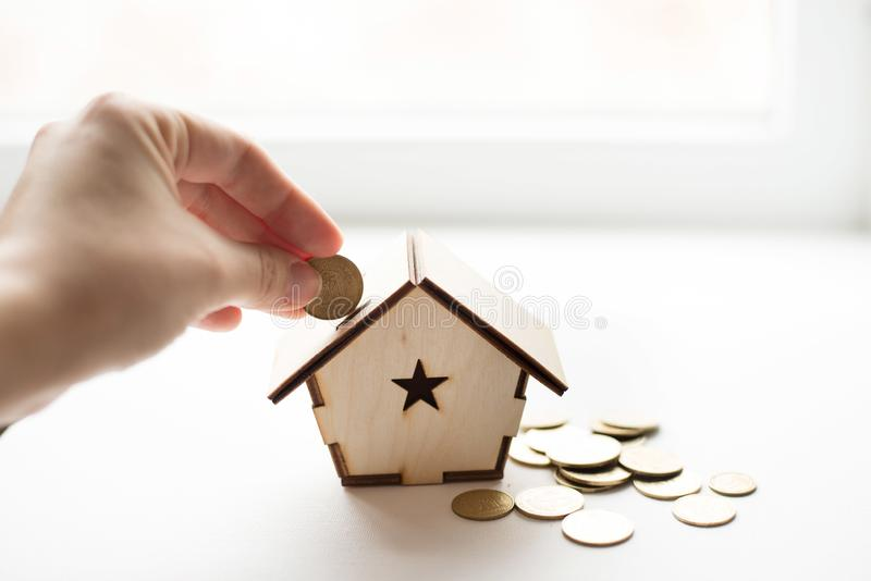 Closeup of hand putting coin in wood house piggy bank on white background. place for text. Saving money, home loan, mortgage, a stock photos