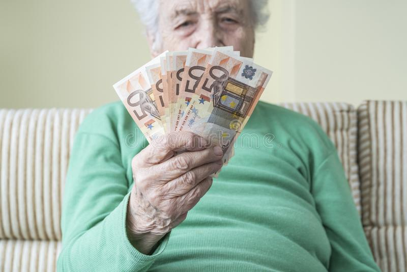 Closeup hand of a senior woman holding euro banknotes stock photos
