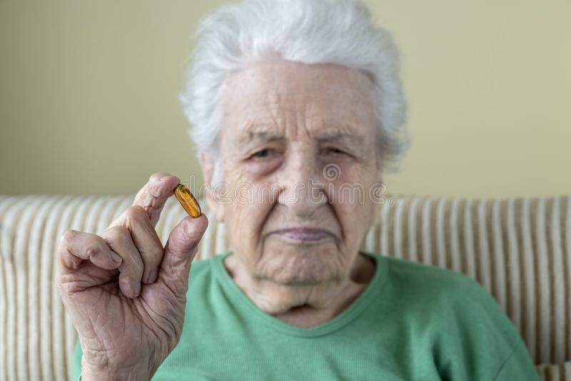 A senior woman holding a vitamin capsule stock image