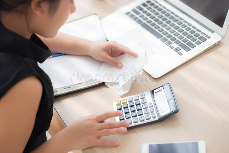 Closeup hand woman calculating expenses household and writing notebook on desk, girl checking bill and stress and note. Female worry debt and tax, finance and royalty free stock photo