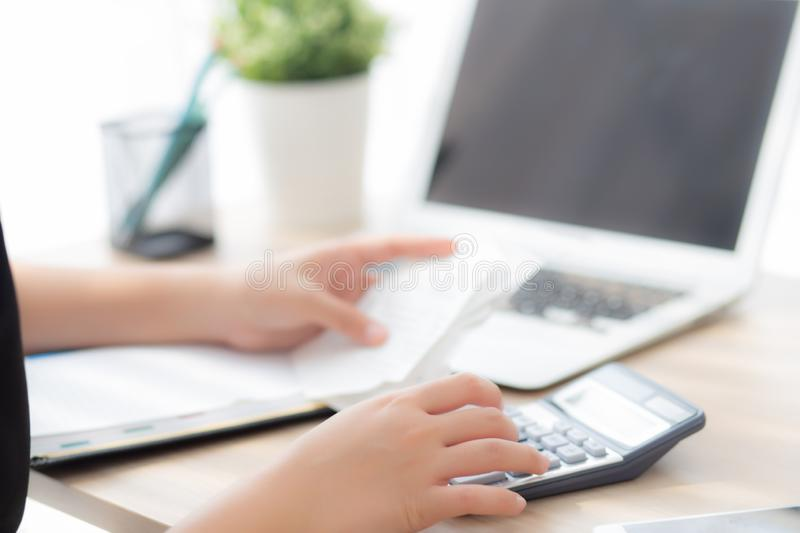 Closeup hand woman calculating expenses household and writing notebook on desk, girl checking bill and stress and note. Female worry debt and tax, finance and royalty free stock image