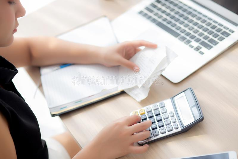 Closeup hand woman calculating expenses household and writing notebook on desk. Girl checking bill and stress and note, female worry debt and tax, finance and stock image