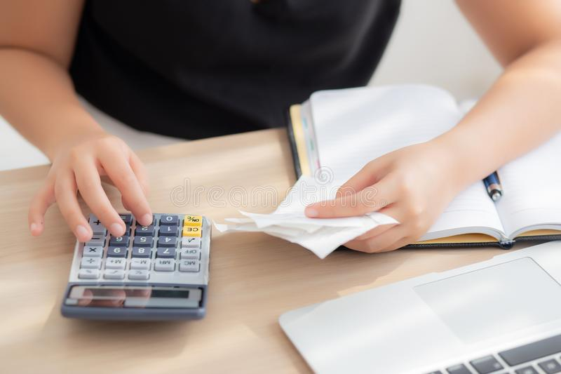Closeup hand woman calculating expenses household and writing notebook on desk, girl checking bill and stress and note. Female worry debt and tax, finance and stock photo