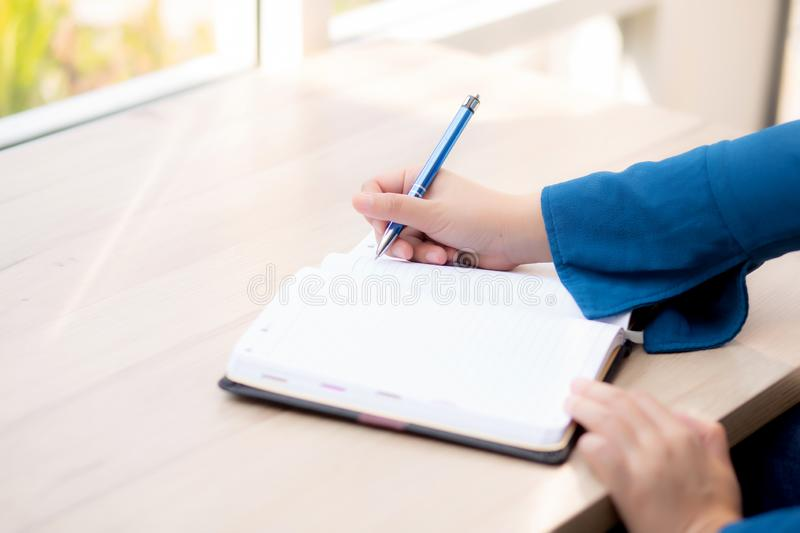 Closeup hand woman writer thinking idea and writing on notebook or diary with happy, lifestyle of asian girl is student stock photos