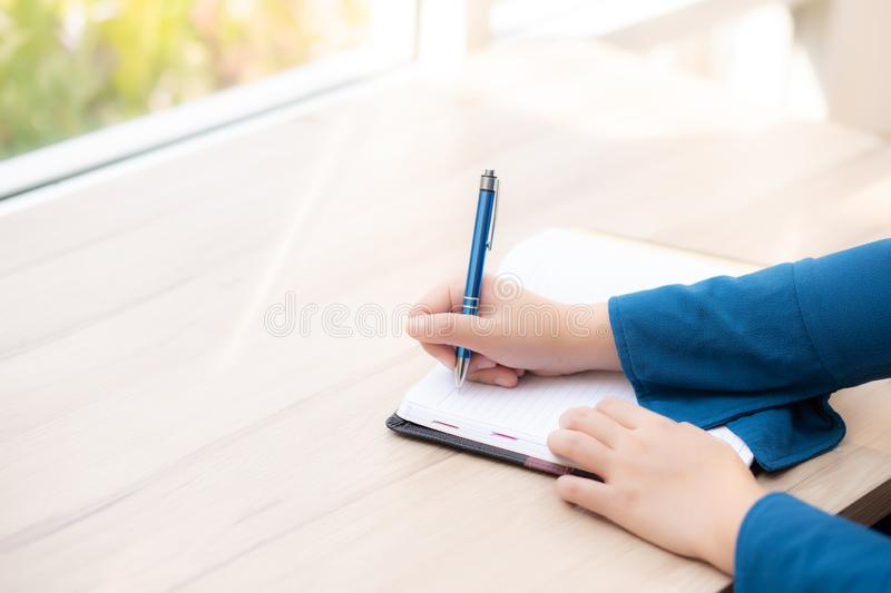 Closeup hand woman writer thinking idea and writing on notebook or diary with happy stock photo