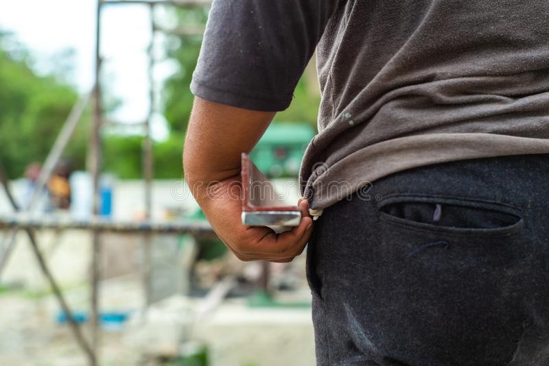 Closeup hand of worker holds the reinforcement steel plate with blurred scaffolding in background at the construction site.  stock images