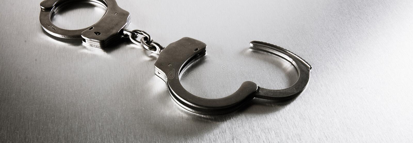 Closeup of handcuffs on obscure stainless steel background for prison. Closeup of handcuffs on obscure stainless steel background for concept of risk of prison royalty free stock photos