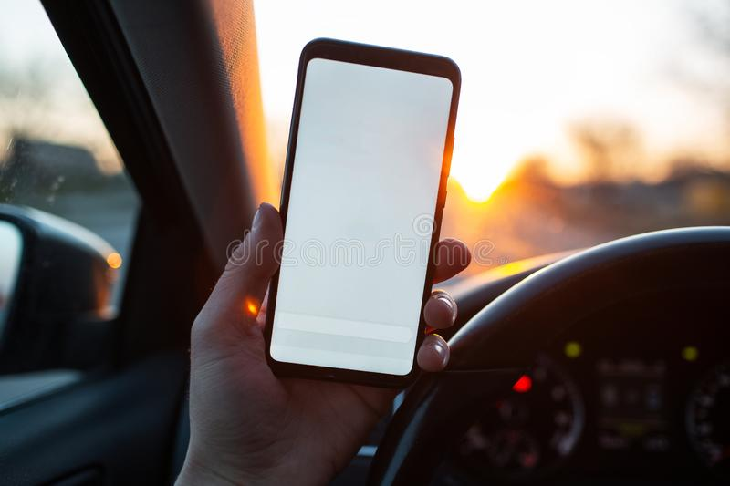 Closeup of handing smartphone with mockup in the car stock photography