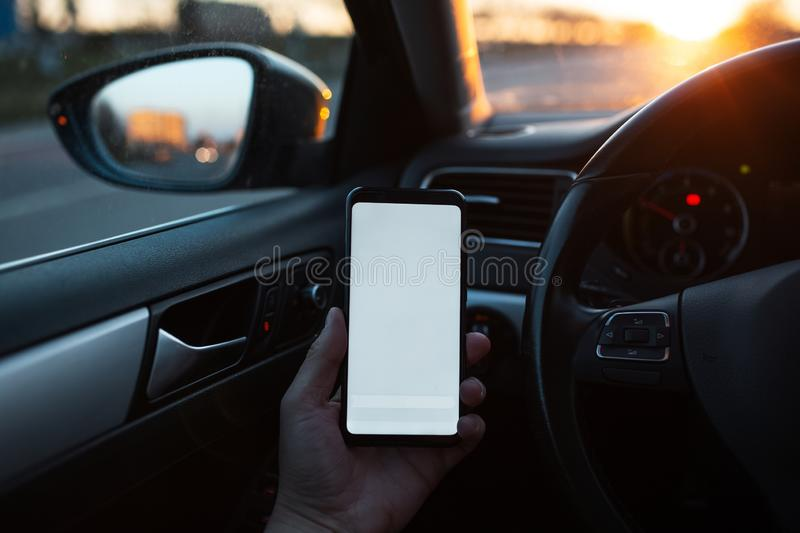 Closeup of handing smartphone with mockup in the car stock photo