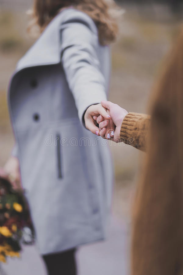 Closeup hands' portrait of beautiful young couple love each ot. Closeup portrait of hands young girl and guy with blond hair kisses, show love royalty free stock images