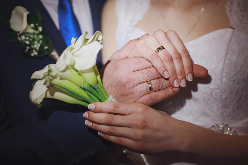 Closeup of hands of bridal couple with wedding rings. Bride holds wedding bouquet of white flowers stock photography