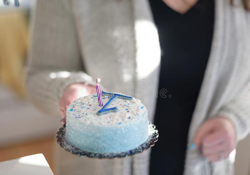 Closeup of hands carrying birthday cake with candle for baby`s f. Closeup of mother carrying first birthday cake with lit candle royalty free stock photo