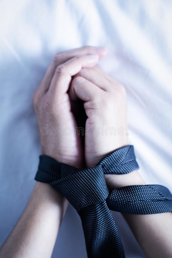 Man tied up with a necktie. Closeup of the hands of a caucasian man, lying face up on a bed with white linen, tied up with a gray necktie royalty free stock image