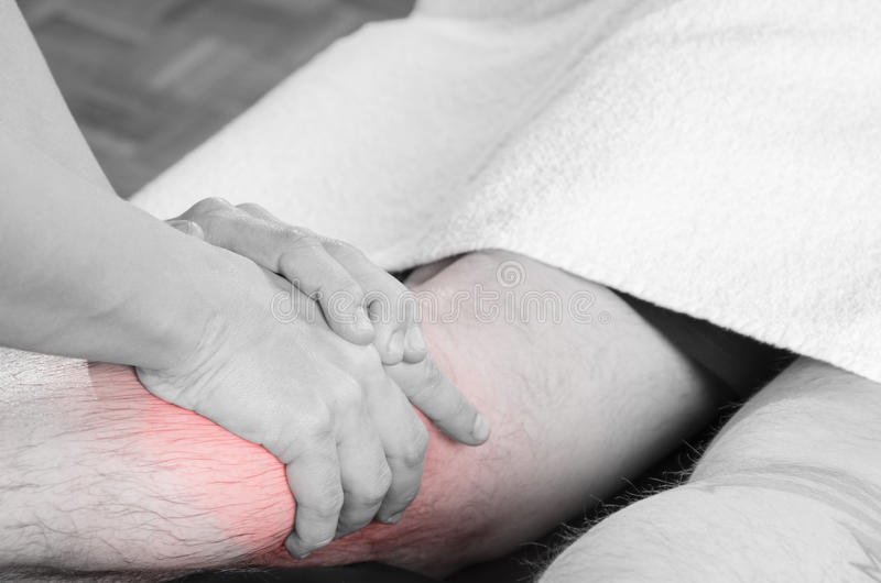 Closeup of hands of chiropractor/physiotherapist doing calf muscle massage to man patient, in silhouette studio. Red color pain. royalty free stock images