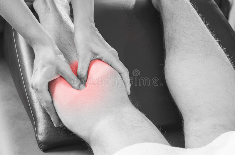 Closeup of hands of chiropractor/physiotherapist doing calf muscle massage to man patient, in silhouette studio. Red color pain. stock photos
