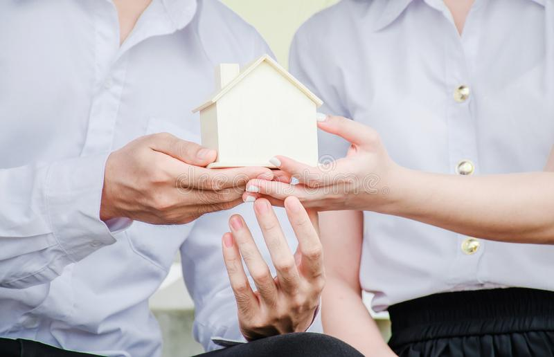 Closeup hands of an couple students holding a little house together, Concept of sustaining a house between two people. stock photo