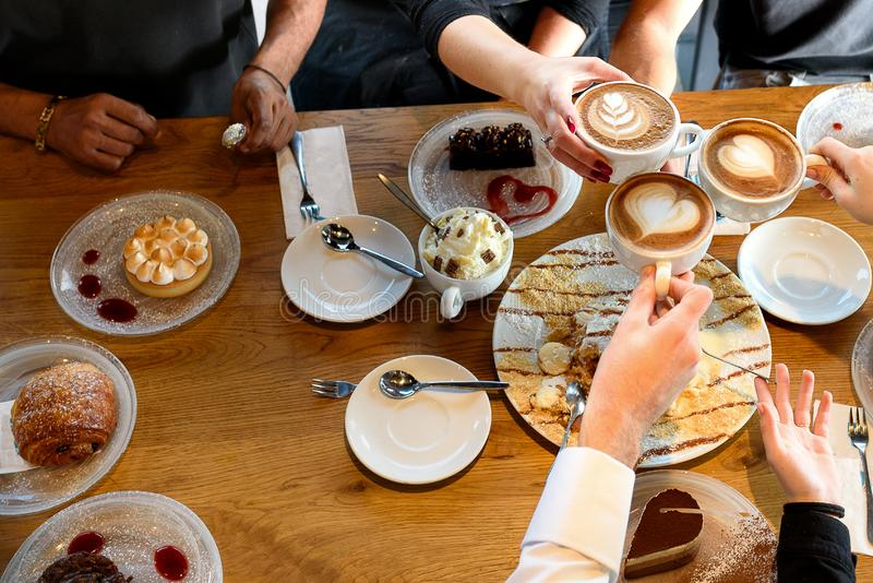 Closeup of hands with desserts and coffee cups in a cafe stock photos