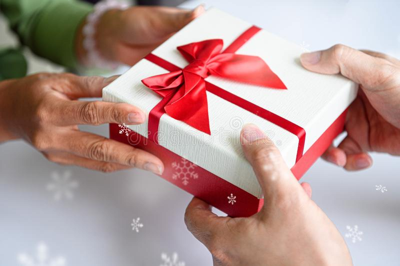 Closeup of hands giving gift box in Christmas day and new year festival to each other. Holiday and event. Surprising giftbox in royalty free stock images
