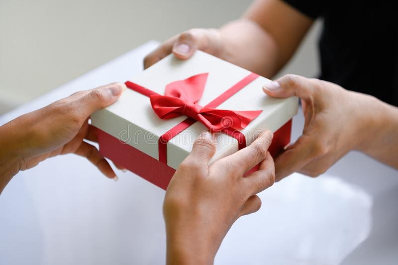 Closeup of hands giving gift box in Christmas day and new year festival to each other. Holiday and event. Surprising giftbox in royalty free stock photo