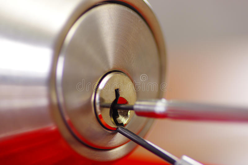 Closeup hands of locksmith using metal pick tools to open locked door.  royalty free stock photo