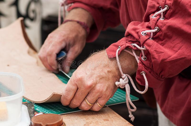 Hands of man working leather at the medieval market. Closeup of hands of man working leather at the medieval market royalty free stock photo