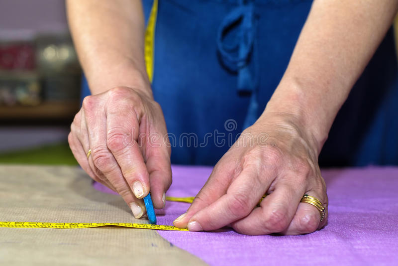 Closeup of hands of seamstress. Working stock image