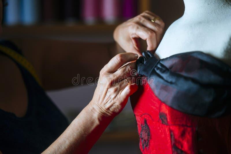 Closeup of hands seamstress working. Closeup of hands of seamstress working in the tailoring royalty free stock image