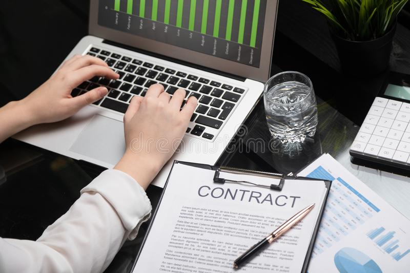 Closeup of hands typing on laptop lying next to contract royalty free stock photo