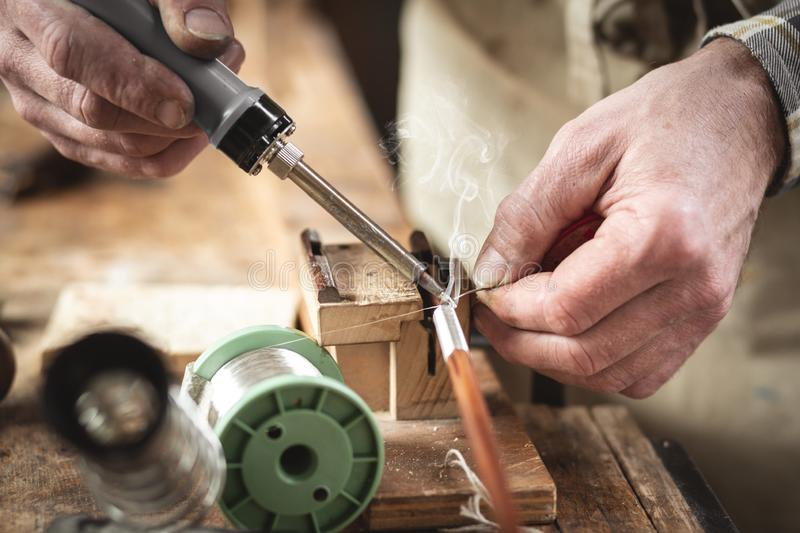Applying a soldering iron on a rustic workbench. Closeup of hands using a soldering iron on a rustic workbench. The person is working on the wire winding of a royalty free stock images