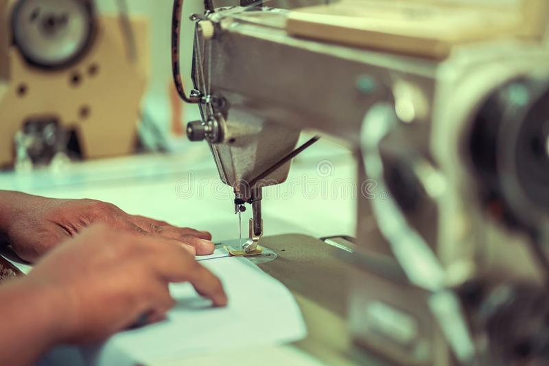 Closeup hands worker stitching white fabric on sewing machine. Needle, textile, fashion, industry, process, hobby, thread, seamstress, clothes, foot, jeans royalty free stock photography