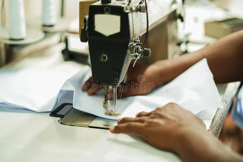 Closeup hands worker stitching white fabric on sewing machine. Needle, textile, fashion, industry, process, hobby, thread, seamstress, clothes, foot, jeans royalty free stock images