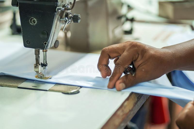 Closeup hands worker stitching white fabric on sewing machine. Needle, textile, fashion, industry, process, hobby, thread, seamstress, clothes, foot, jeans stock image