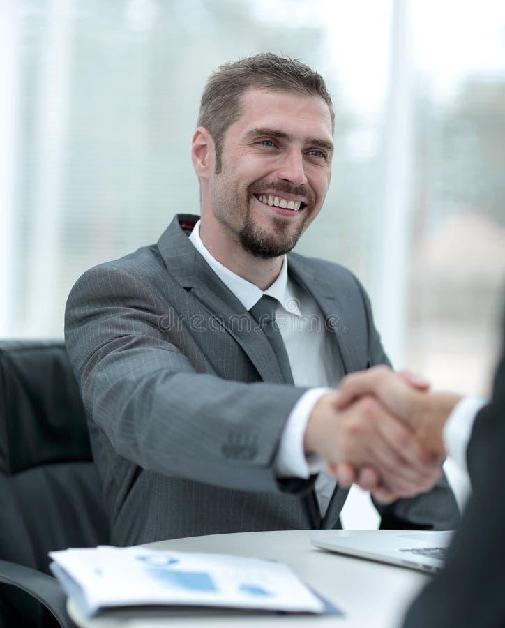 Closeup .handshake of business partners above the Desk stock photo