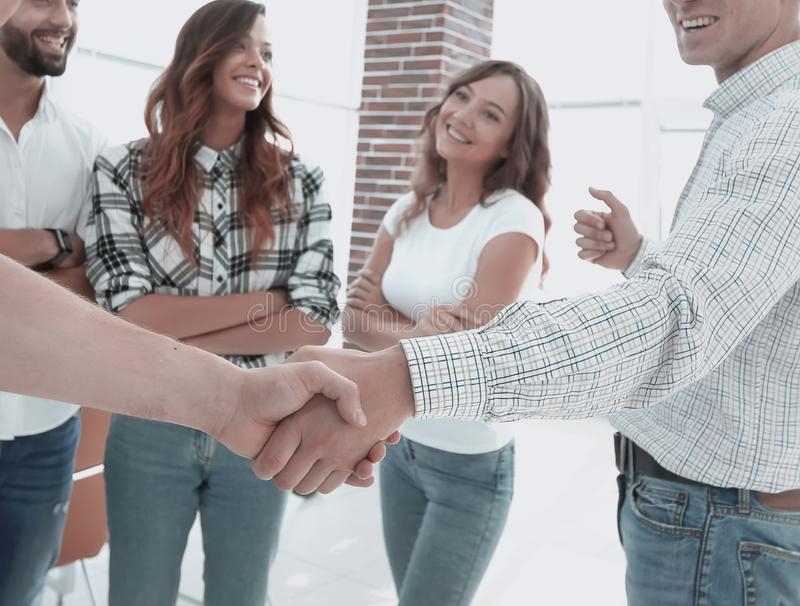 Closeup of handshake business people. On the background of the creative team stock photos