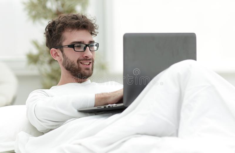 Handsome man working on laptop lying on bed royalty free stock photo