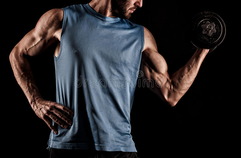 Closeup of a handsome power athletic man bodybuilder doing exercises with dumbbell. royalty free stock images