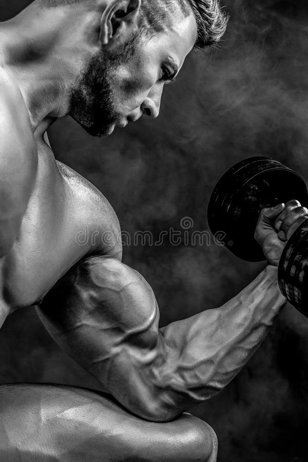 Closeup of a handsome power athletic man bodybuilder doing exercises with dumbbell. Fitness muscular body on dark royalty free stock images