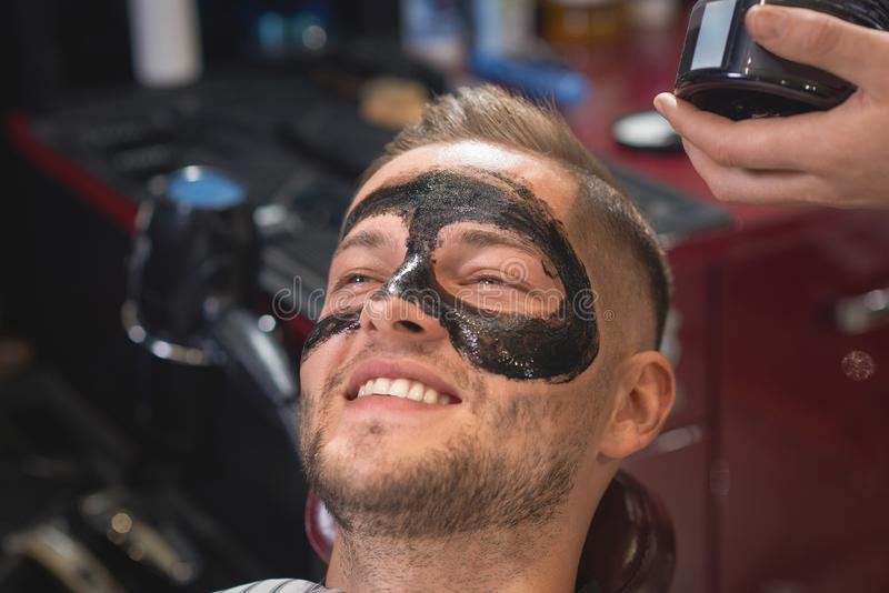 Closeup of happy man with black mask on face in barber shop. Closeup of handsome smiling men with black mask against dots on face lying on chair in barber shop royalty free stock photography