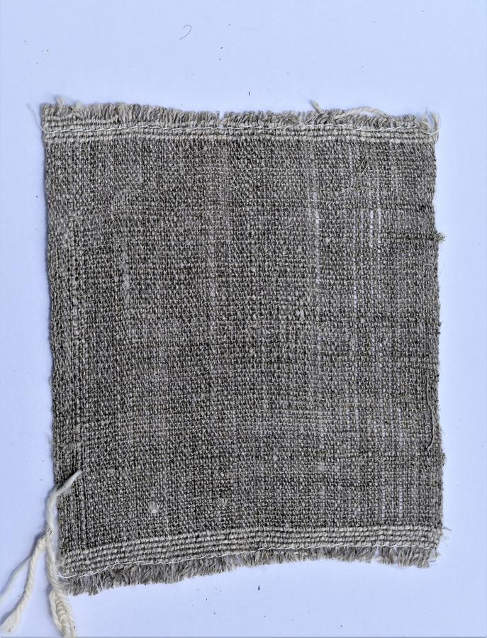 Closeup of handwoven hand-spun linen cloth. Spinning. Textiles. Weaving. Closeup sample of undyed handspun handwoven linen cloth on light background. Sample was stock images