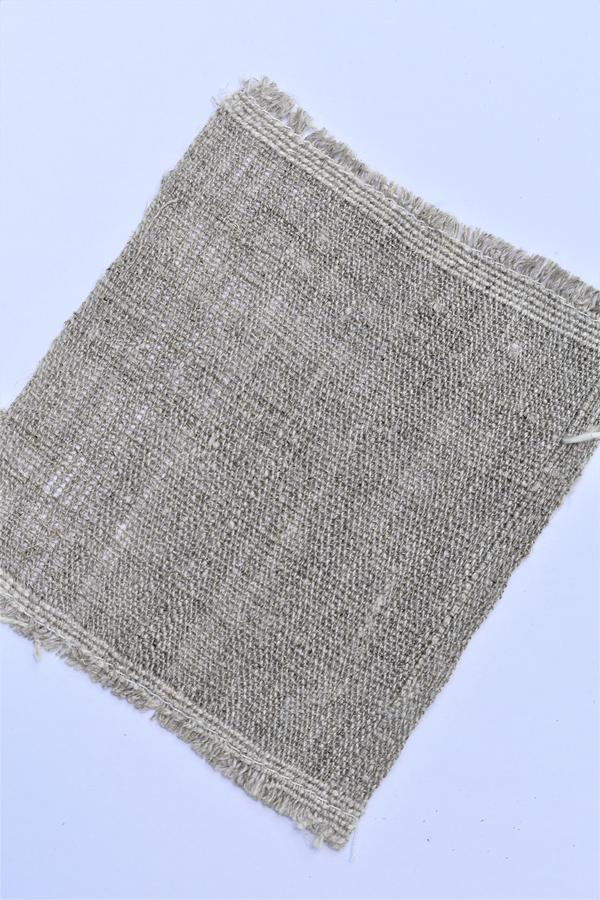 Closeup of handwoven hand-spun linen cloth. Textiles. Weaving. Spinning. Closeup sample of undyed handspun handwoven linen cloth on light background. Sample was stock photo