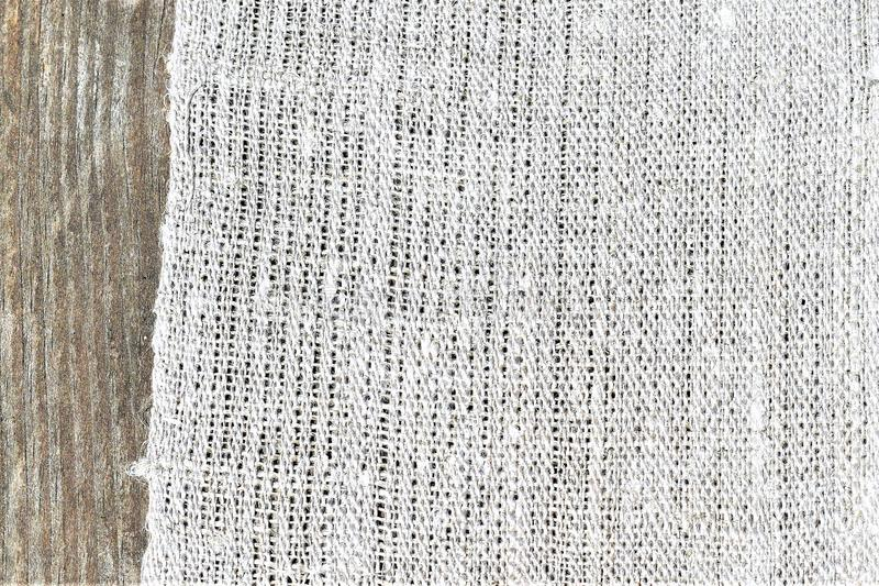 Weaving. Closeup of handwoven hand-spun linen cloth. Textiles. Closeup sample of undyed handspun handwoven linen cloth on wooden background. Weaving royalty free stock photos