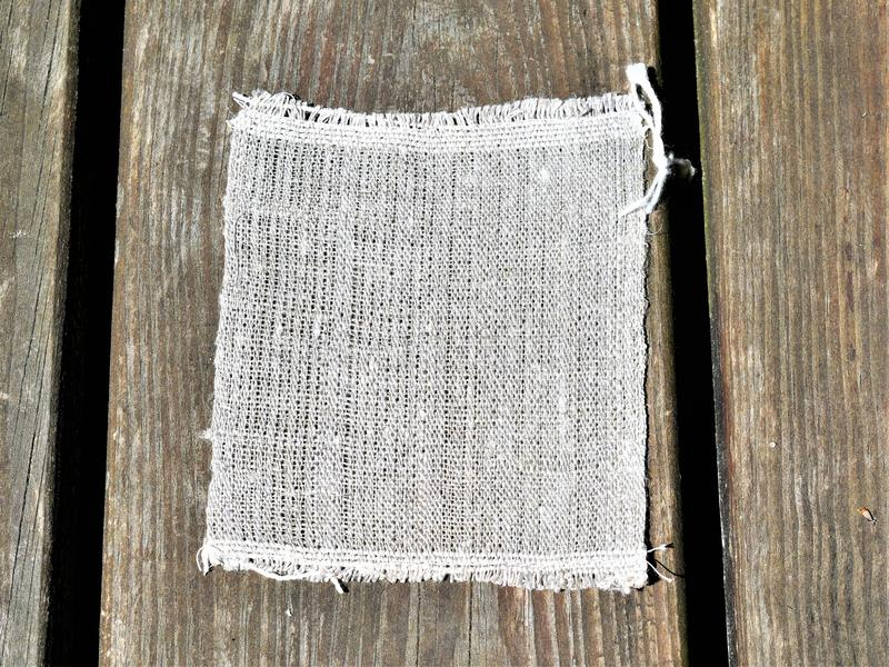 Closeup of handwoven hand-spun linen cloth. Textiles. Weaving. Closeup sample of undyed handspun handwoven linen cloth on wooden background. Sample was cut off stock photography