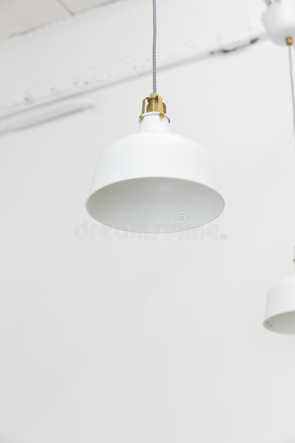 Closeup of hanging white ceiling lamp on wall background. Close up of hanging white ceiling lamp on wall background stock images