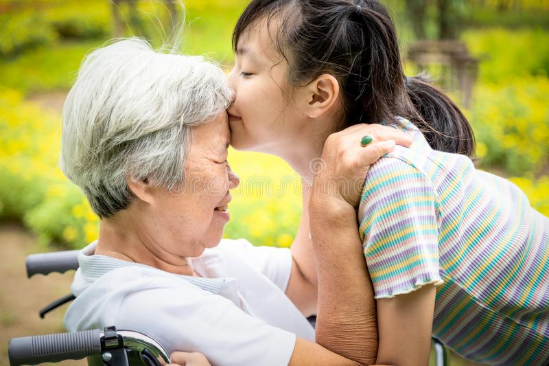 Closeup,Happy asian elderly woman with beautiful child girl hugging,kissing,smiling in summer,love of granddaughter with senior royalty free stock photos