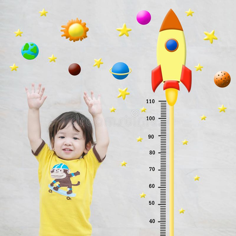 Closeup happy asian kid stand for measure height with cute cartoon at the marble stone wall textured background in growth of kid c. Closeup happy kid stand for stock photography