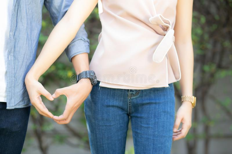Closeup of happy couple fun making gesture heart shape with hand outdoor together stock images
