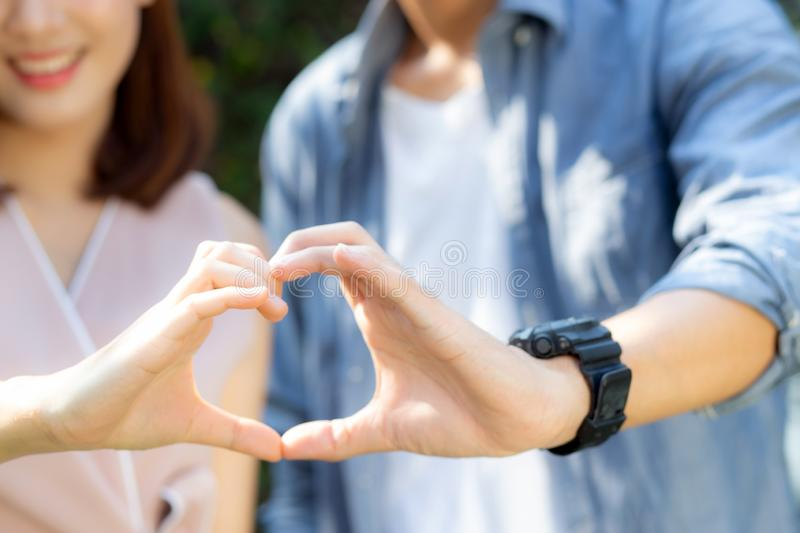 Closeup of happy couple fun making gesture heart shape with hand outdoor together stock image