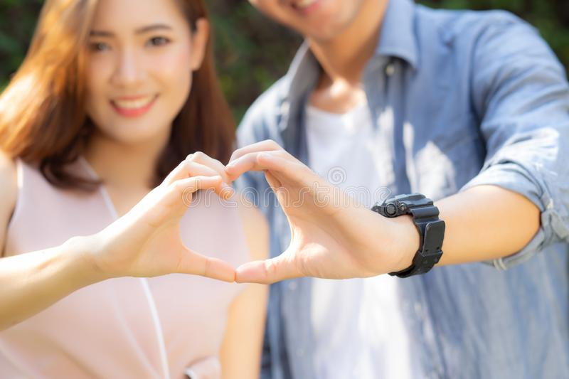 Closeup of happy couple fun making gesture heart shape with hand outdoor together royalty free stock images
