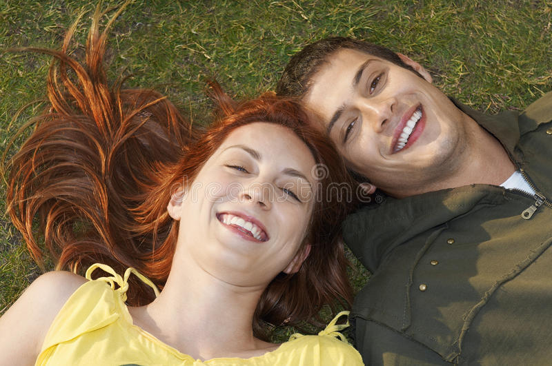 Closeup Of Happy Couple Lying On Grass. High angle portrait of happy couple lying on grass at park stock photography